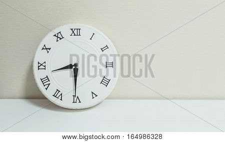 Closeup white clock for decorate show half past eight or 8:30 a.m. on white wood desk and cream wallpaper textured background with copy space