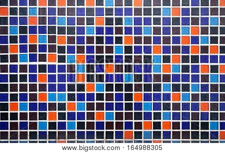 Blue and orange tiled floor with water drops pattern background. Wet small square colorful tiles on the bathroom wall
