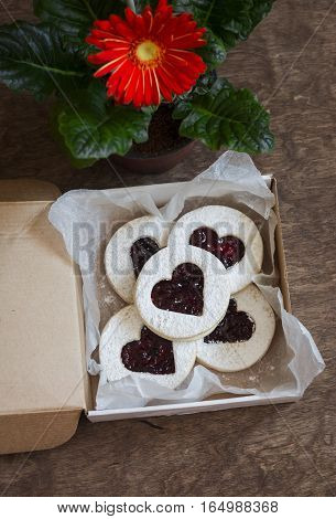 Valentine's day cookies-hearts with jam in the box and gerbera flower on wooden table top view.