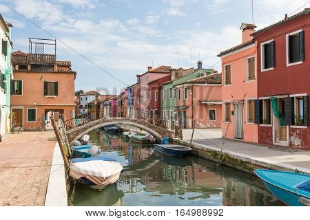 Tranquil scene of canal on the island of Burano. Colorful houses are on both sides of the canal (Venice Italy). All potential trademarks are removed.