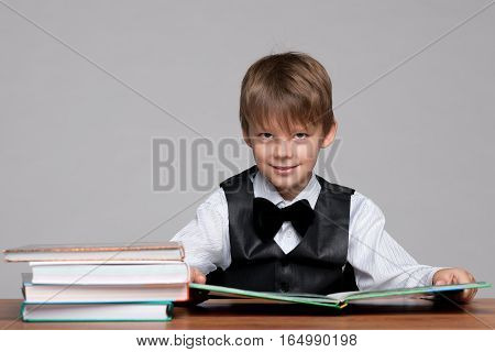Young Boy At The Desk Reads A Book