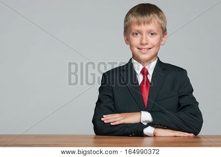 Young Smiling Boy At The Desk