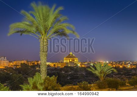 Mosta Malta - The Mosta Dome or The Church of the Assumption of Our Lady commonly known as the Rotunda of Mosta with palm tree by night