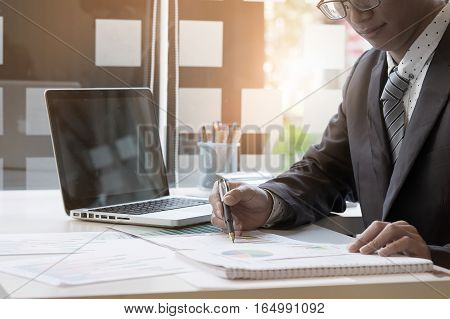 Businessman discussing the analysis charts or graphs on modern White office desk table vintage tone.