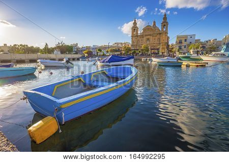 Msida Malta - Blue traditional fishing boat with the famous Msida Parish Church at background on a summer day with blue sky and clouds