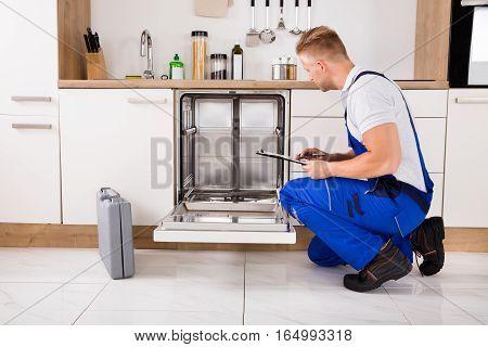 Repairman Sitting Near Dishwasher Writing On Clipboard In Kitchen
