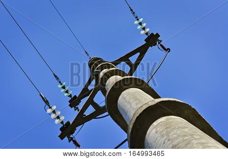 Closeup of concrete electric pylon and cloudy sky