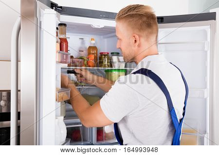 Young Repairman Repairing Refrigerator With Screwdriver In Kitchen