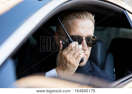 Man Sitting Inside Car Doing Surveillance Talking On Walkie Talkie