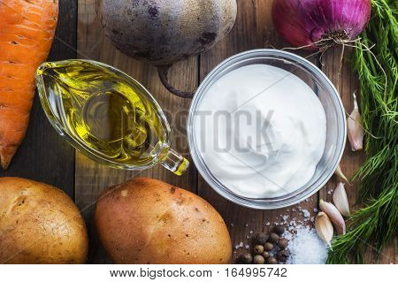 Ingredients for cooking beets potatoes carrots onions garlic dill butter and sour cream. Ingredients for borsch or beetroot. Organic vegetables close-up view from above. Top view flat lay.