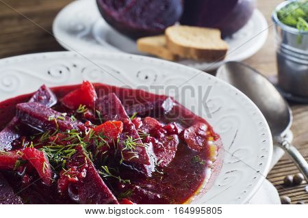 Vegetable soup - red borsch in a white bowl on a rustic wooden background clouse up. Healthy beetroot soup vegetarian food. Delicious beet soup with croutons.