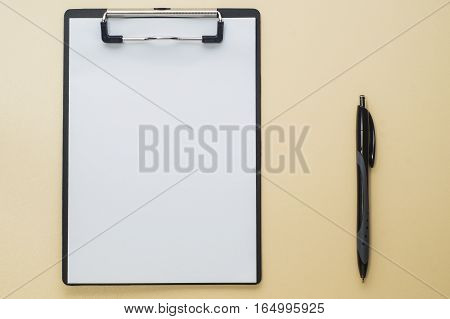 Blank paper on black clipboard with copy space on beige background. Folder with blank paper design mockup. Document holder mock up template.