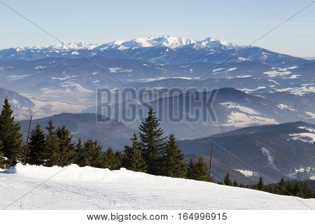 Winter mountain landscape - top view of snow covered valley in the background fog and mountain peaks. View from the ski slopes - skiing resort Kubinska Hola; Western Tatras. Slovakia. Travel destination for winter vacations and skiing.