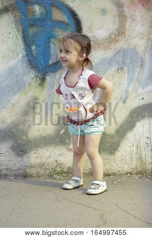 Positive kid. Happy little girl 2-3-4 years old with braids on her head stands and smiles in the street near a concrete wall