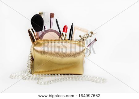 Women's cosmetics. Gold cosmetic bag with a set of cosmetics to create a make-up. Copy space.