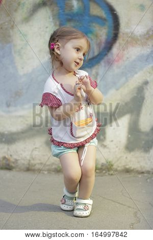 Shy kid girl with pigtails on a background of a concrete wall with graffiti