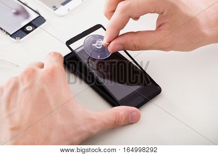 Close-up Of A Person's Hand Repairing Broken Mobile Phone Screen