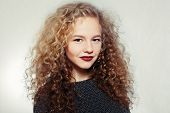 people youth and beauty concept - Beauty young woman with curly big and long hair. Permed hair. Glamour lady Beauty Girl on grey background. Beautiful Woman Portrait. Blond Wavy Hair poster
