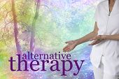Come and try our Alternative Therapies -  female holistic therapist gesturing to the words ALTERNATIVE THERAPY on a colorful rainbow tinted tree scenery background with copy space poster