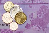 Several euro coins on a euro banknote poster