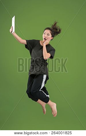 Gadget In Modern Life. Jump Of Young Woman Over Green Studio Background Using Laptop Or Tablet Gadge