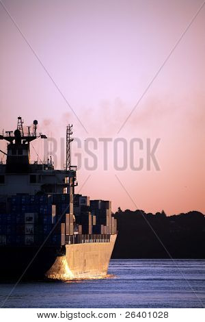 cargo container ship heading out to sea at sunset - large freighter