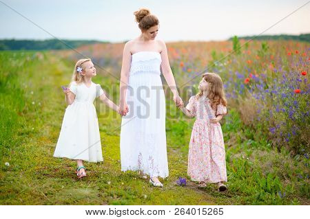 Young Mother Wearing White Dress With Two Children Walking Near The Poppies Field