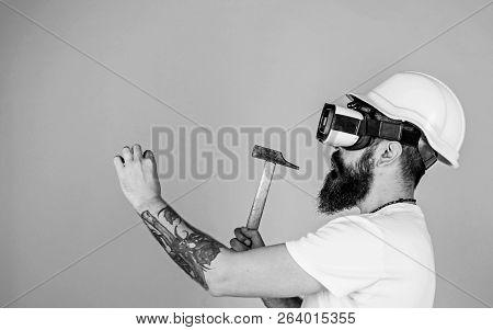 Builder And Renovation Concept. Man With Beard In Vr Glasses Holds Hammer, Light Blue Background. Hi