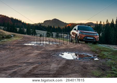 Apuseni, Romania - Oct 15, 2017: Orange Suzuki Vitara Suv Parked On The Country Road Near Forest In