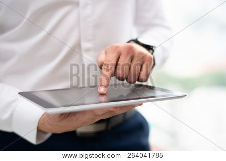 Close-up Of Male Manager Working On Digital Tablet. Caucasian Man Networking Or Browsing On Pc Table