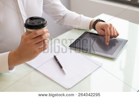 Hands Of Businessman Using Digital Tablet And Holding Coffee. Caucasian Man Sitting At Table With Bl