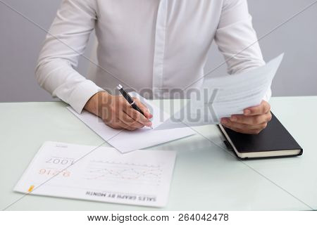 Young Businessman Sitting At Table And Working With Papers. Caucasian Manager Sitting At Table, Look