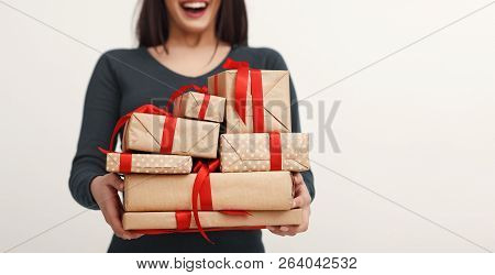 Young Excited Woman Holding Heap Of Gifts, Girl Got Lot Of Birthday Presents, White Background. Holi