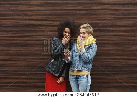 Surprised Multiethnic Female Friends Browsing News On Smartphone, While Having A City Walk, Outdoors