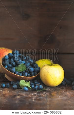 Autumn Harvest Blue Sloe Berries And Apples On A Wooden Table Background. Copy Space. Dark Rustic St