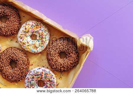 Delicious Glazed Donuts In Box On Violet Surface. Flat Lay Minimalist Food Art Background. Top View.