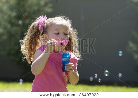 Girl blowing bubbles at the park