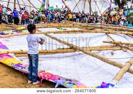 Santiago Sacatepequez, Guatemala - November 1, 2017: Boy Untangles His Kite From Fallen Giant Kite A