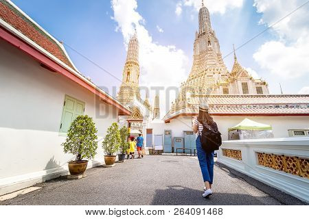 Tourist Women With Carrying A Backpack Viewing Poster, About The Temple In Bangkok At Arunratchawara
