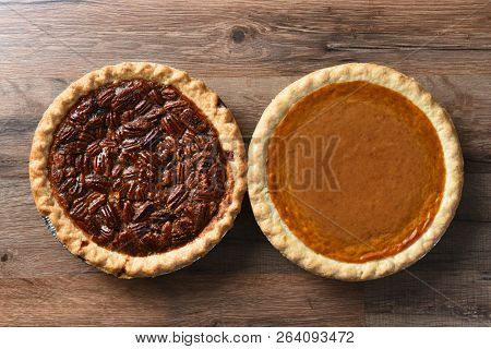 Top View of a fresh baked pumpkin pie and a pecan pie on a rustic wood table, for Thanksgiving feast.