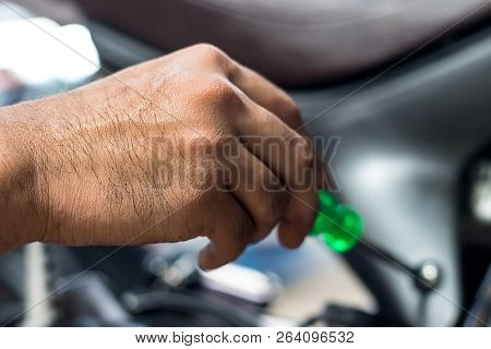 People Are Repairing A Motorcycle Use A Wrench And A Screwdriver To Work. Use The Wrench To Tighten