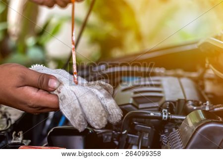 Mechanic Repairing Car With Hand Of Car Mechanic Checking Level Engine Oil For Maintenance .