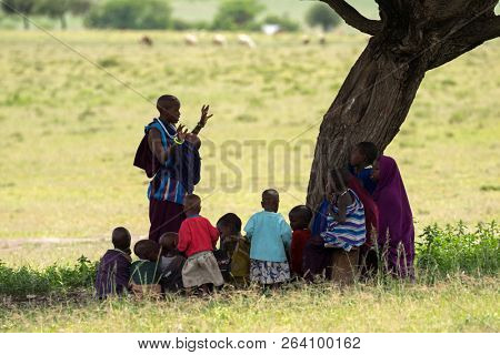 TANZANIA, EAST AFRICA - APRIL 2018 : Maasai woman, female teacher teaching young African kids sitting in shade of under Acacia tree as outdoor school on April 13, 2018 in Tanzania, East Africa.