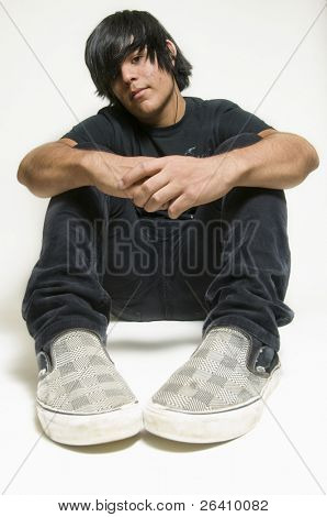 Teen boy dressed in black sitting on white background