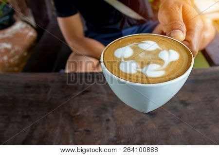 A Man Holding A Glass Of Coffee Latte In Hand On A Wooden Table.