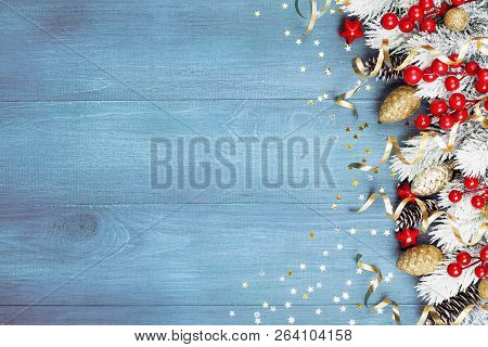 Christmas Background With Snowy Fir Tree And Holiday Decorations On Blue Wooden Table Top View. Gree
