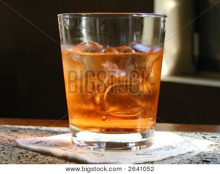A whisky glass is at the bar with a