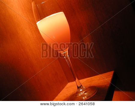 A cocktail in a champagne glass is at