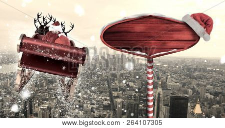 Digital composite of Santa in sleigh with reindeer flying and Christmas sign over city