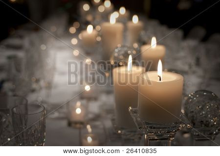 Warm candle lit table set for many